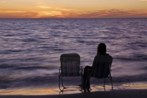 9028120-lonely-girl-sitting-on-a-beach-chair-at-sunset